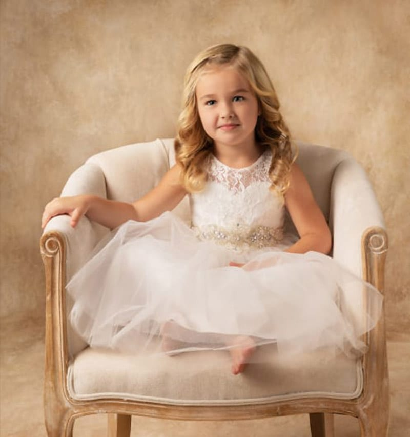 Classical Portrait of little girl in a dress on a chair